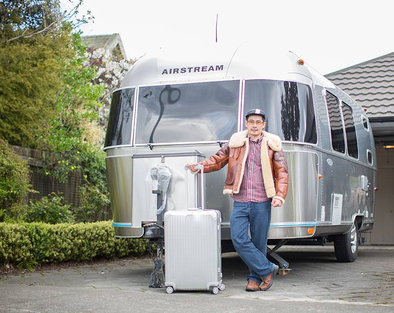 Joseph Ku posing in front of the Airstream